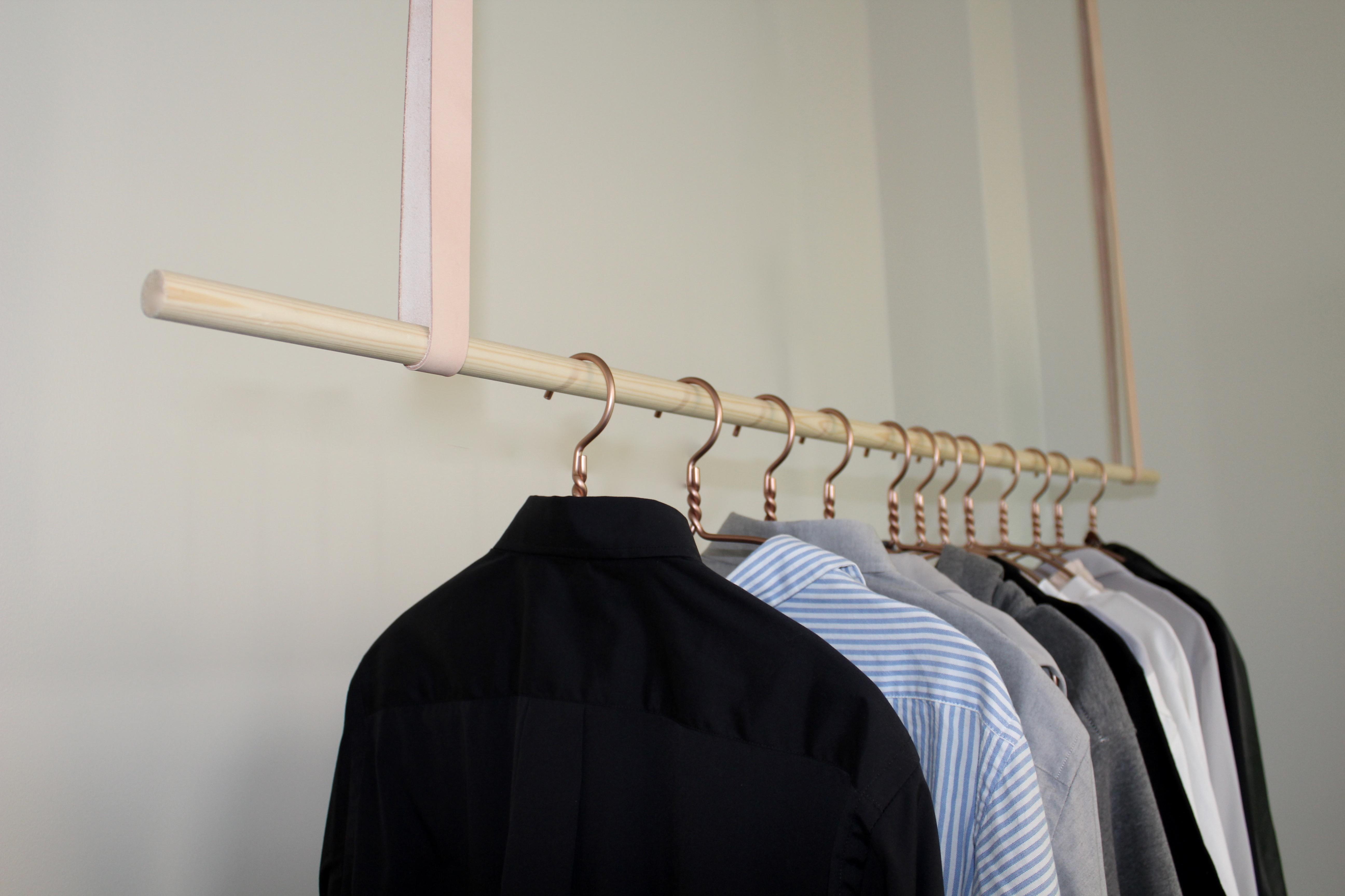Tøjstativ med metalstang i læderremme hængende ned fra loftet