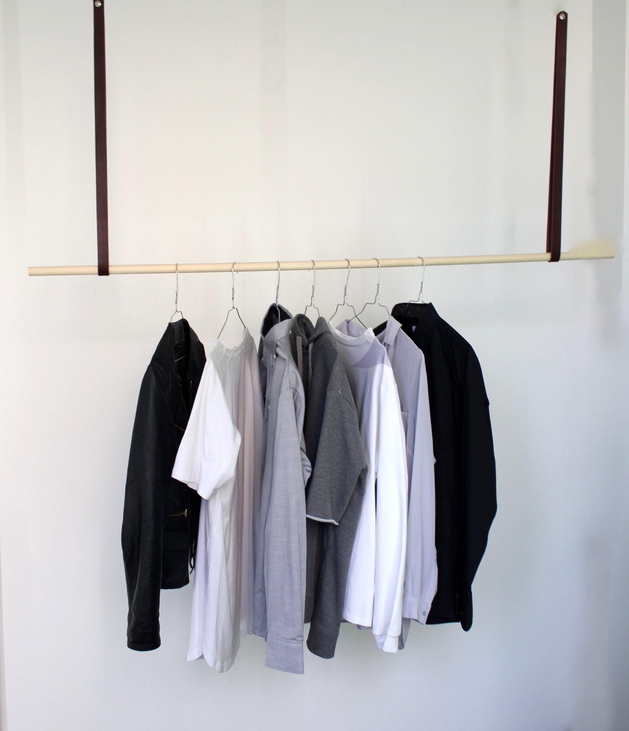 Tøjstativ med mørkebrune læderremme og træstang
